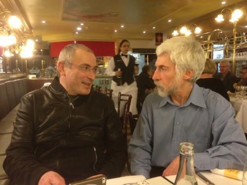 """Михаил Ходорковский (слева) и журналист """"МК"""". Официантка несёт бутылку белого (налево) и рюмку красного (направо)."""