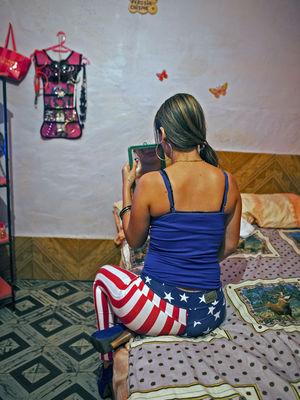 Проститутка в своей комнате в борделе в Пуэрто-Кабельо, Венесуэла, 28 мая 2014 года. Фотограф: Владимир Маркано / Bloomberg