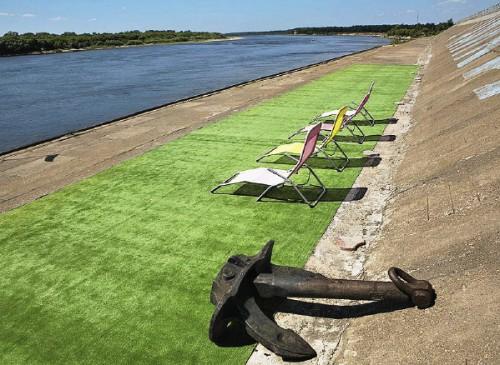 Место для принятия «солнечных ванн»: чтобы не обжечь ноги о разгоряченный бетон, на него положили пластиковый зеленый газон.