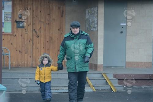 Виталий Безруков выходит с внуком Иваном на прогулку из своего подъезда в Москве